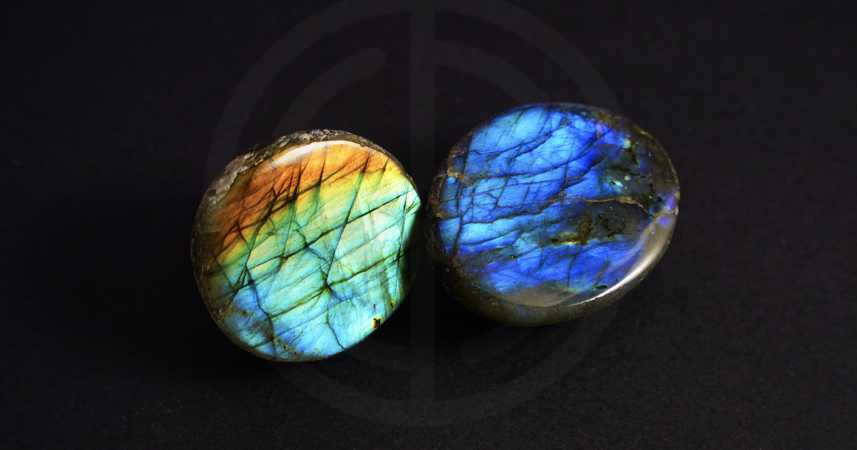 Two labradorite gemstones on dark background